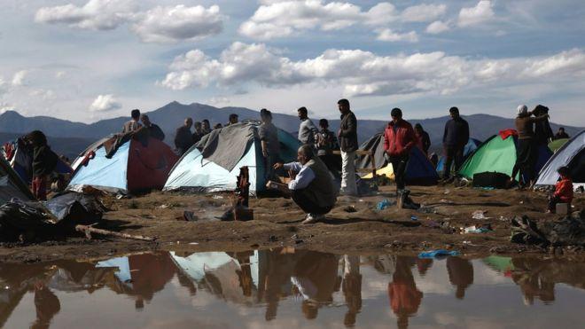 Беженцы и мигранты стоят перед своими палатками после ночного шторма в лагере беженцев Идомени, недалеко от греческой границы с Македонией, северная Греция, 8 марта 2016 года
