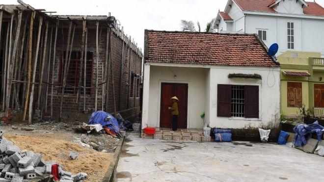A Vietnamese woman stands near an under-construction house in Yen Thanh district