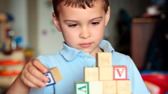 Мальчик с аутизмом играет с кирпичами