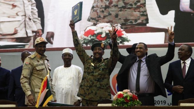 "Protest leader Ahmed al-Rabie (2nd-R) alongside Lt-Gen Abdel Fattah Abdelrahman Burhan (C), head of Sudan's ruling Transitional Military Council during the signing ceremony in Khartoum on August 17, 2019, accompanied by General Hamdan Daglo ""Hemeti"" (2nd-L), TMC deputy chief and commander of the Rapid Support Forces paramilitaries, Ethiopian Prime Minister Abiy Ahmed (L), and Chadian President Idriss Deby (3rd-L)"