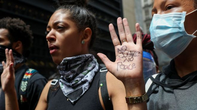 Woman in New York holding hands up as part of a protest