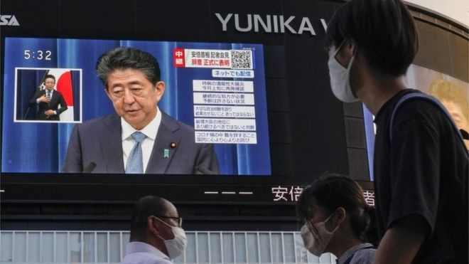 People walk past a display at Shinjuku, showing Japanese Prime Minister Shinzo Abe announcing his resignation during a televised news conference (28 August 2020)