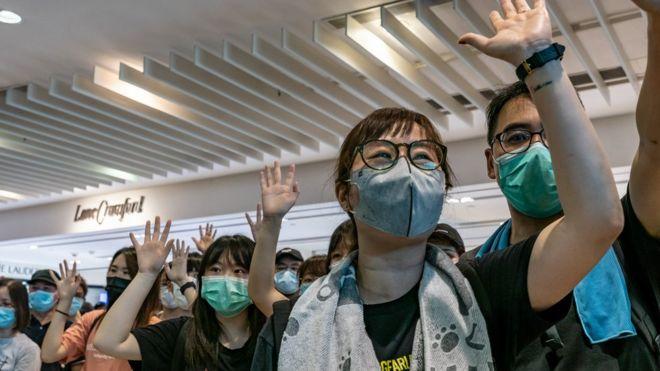"""示威者在商场上英语学习网举起手,表达对""""五大诉求""""的坚持。"""