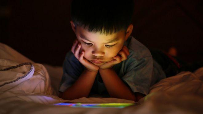 Menino olhando para um tablet