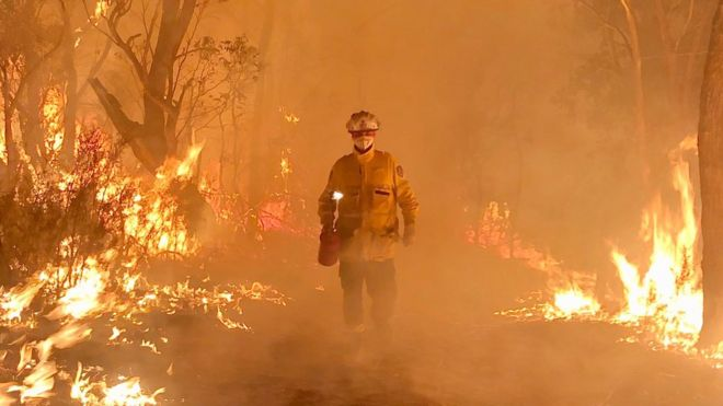 Firefighter Daniel Knox stands amid flaming bushland during a controlled burn in NSW