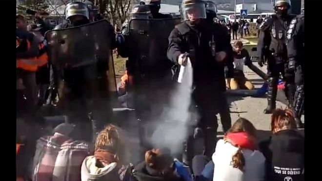 French riot police try to evacuate climate change activists blocking a road at Chambéry airport