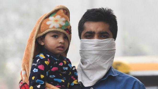 hombre con cara cubierta cargando niño