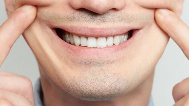 Hombre sosteniendo una sonrisa forzada con las manos