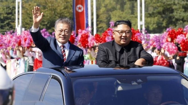 Moon Jae-in (left) and Kim Jong-un wave from an open top car in Pyongyang