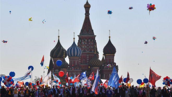 As pessoas celebram 1º de maio com bandeiras, balões, música e dança na Praça Vermelha, em Moscou