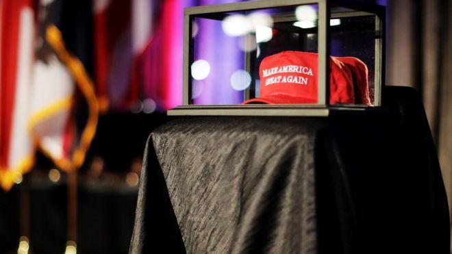 Шляпа «Сделай Америку снова великой» сидит в стеклянном футляре во время вечеринки по выборам кандидата в президенты от Республиканской партии Дональда Трампа в Нью-Йорк Хилтон Мидтаун 8 ноября 2016 года в Нью-Йорке. Американцы сегодня будут выбирать между кандидатом в президенты от республиканцев Дональдом Трампом и кандидатом в президенты от демократов Хиллари Клинтон, когда они пойдут на выборы, чтобы проголосовать за следующего президента Соединенных Штатов. (Фото Чипа Сомодевиллы / Getty Images)