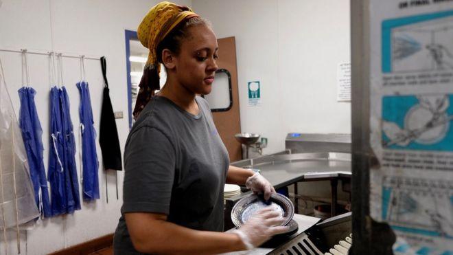 Estudiante universitaria lavando platos