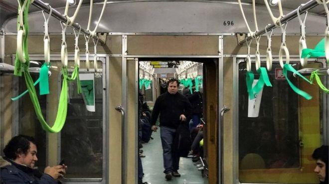 Зеленые ленты, которые символизируют движение за права абортов, видны внутри поезда метро в Буэнос-Айресе, Аргентина, 31 июля 2018 года.
