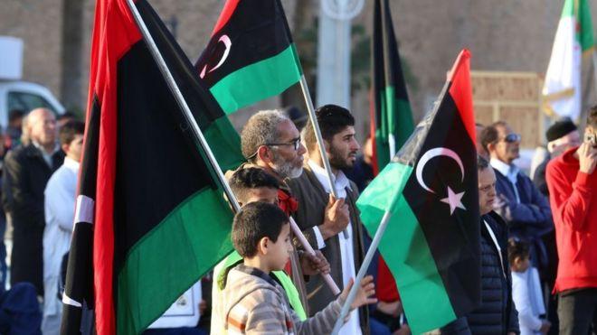 أشخاص من فئات عمرية مختلفة يحملون العلم الليبي