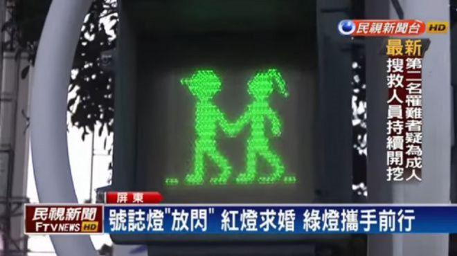 Saat lampu lalu lintas merah, rambu untuk pejalan kaki yang terpampang adalah gambar pria dan wanita yang bergandengan