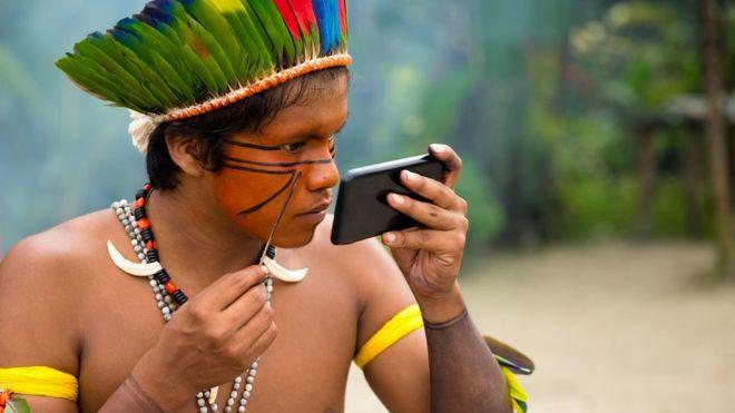 Um indígena da tribo Tupi Guarani no Brasil pinta o rosto