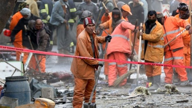 Afghan municipality workers at the scene of a suicide bomb attack in Kabul, Afghanistan, 27 January 2018.