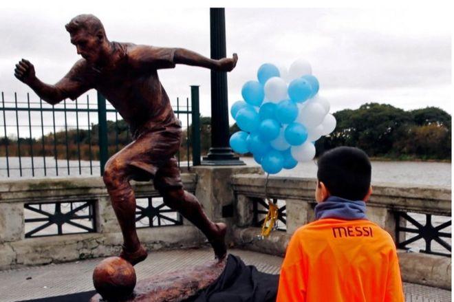 Мальчик носит майку Лионеля Месси, когда он приближается к статуе аргентинского футболиста Месси после того, как она была представлена в Буэнос-Айресе, Аргентина, 28 июня 2016 года.