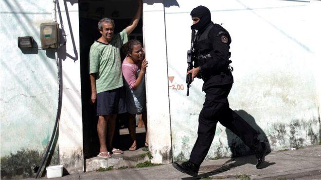 Residentes da Cidade de Deus olham para policial