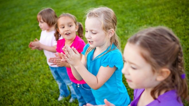 Stock image of four little girls clapping