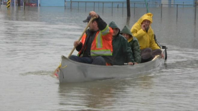 People row a boat through floodwaters