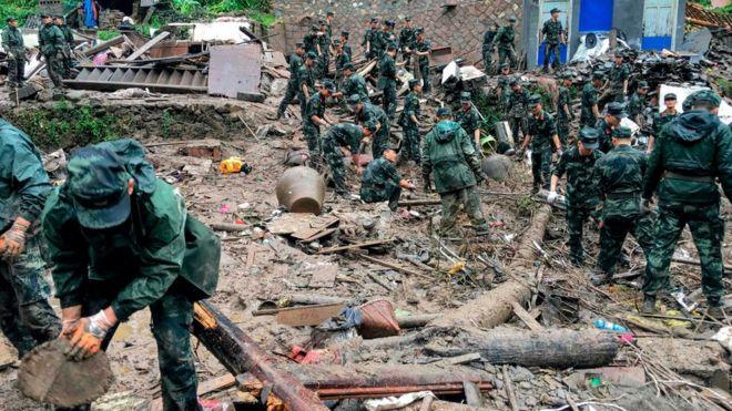 Tim penyelamat mencari korban selamat di puing-puing bangunan yang rusak akibat tanah longsor yang dipicu badai di provinsi Zhejiang, China.