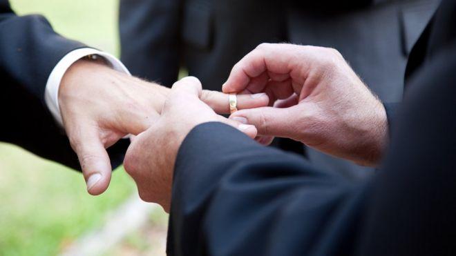 Husbands exchanging wedding rings/same-sex