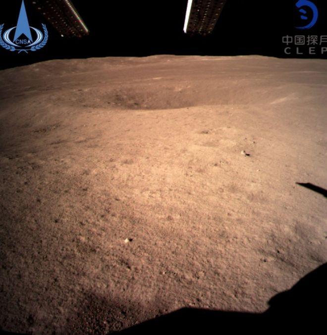 Foto mostra lado desconhecido da Lua. Na imagem, a Lua é vista com uma cor alaranjada. Há um pequeno buraco e, ao fundo, se vê o espaço, preto