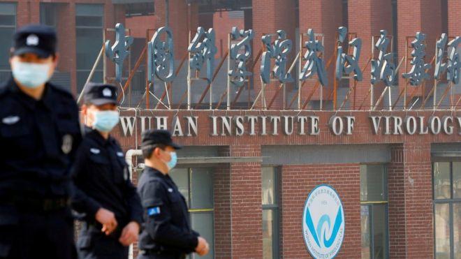 Três agentes fardados e de máscara em frente a fachada com dizeres: Wuhan Institute of Virology