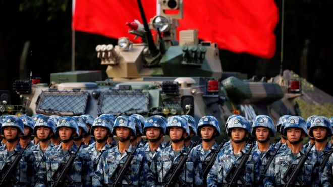 People's Liberation Army (PLA) troops await Xi Jinping at 20th anniversary of city's hand over in Hong Kong. Stand in front of a tank with flag behind