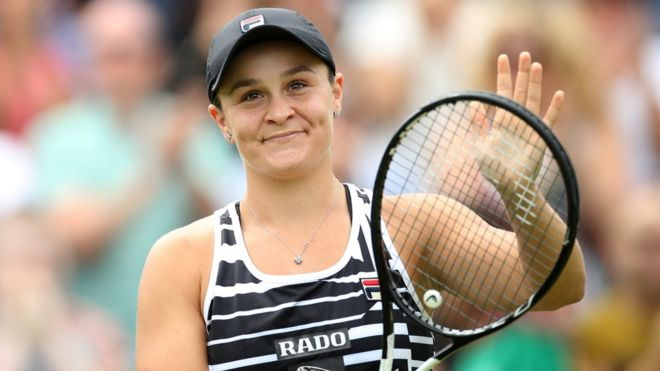 Ashleigh Barty smiles on court and claps with her racquet at Birmingham