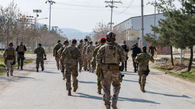 منظر خلفي لجنود الجيش يسيرون على طريق في المدينة