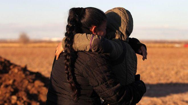 Una mujer abraza a un niño en un lugar cerca de la frontera entre Estados Unidos y México.