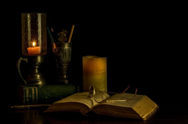 Glasses, candles and an open book