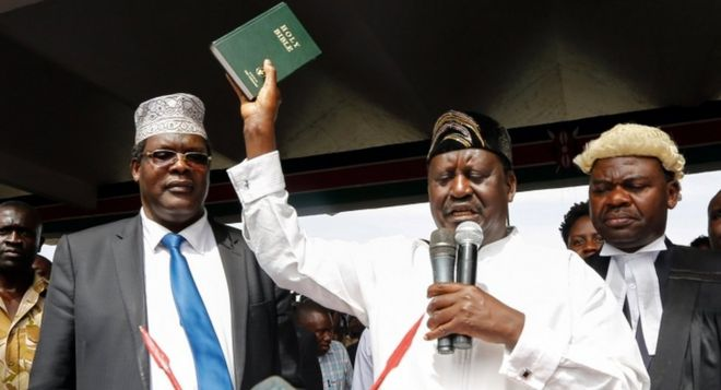 "Raila Odinga raises a bible as he ""takes an oath"" during an unofficial ""swearing-in"" ceremony in Nairobi on 30 January 2018."