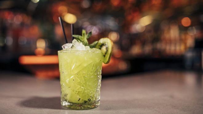 Un trajo con kiwi sin alcohol sobre una barra.