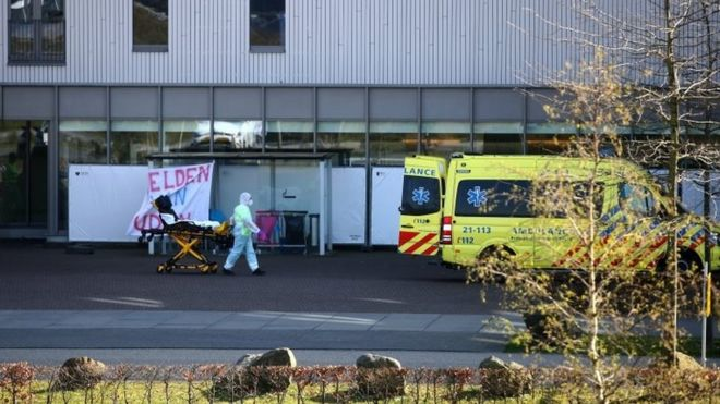 A man in protective gear wheels a stretcher into a hospital in Uden, the Netherlands