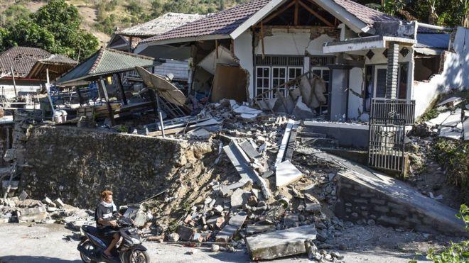 Pengendara Sepeda Motor Melintas Dekat Rumah Yang Roboh Pascagempa Di Desa Bentek Kecamatan Pemenang