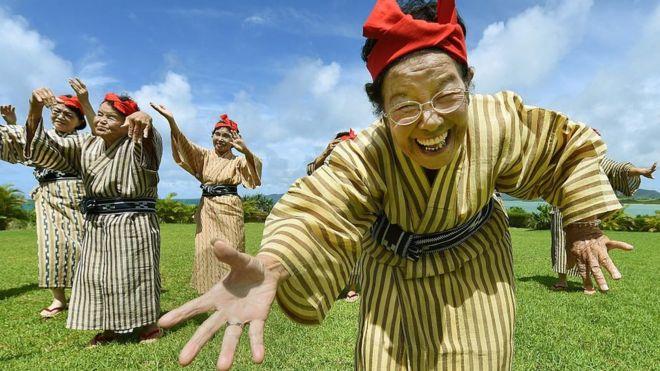 Unas ancianas cantan y bailan usando trajes tradicionales en Okinawa.