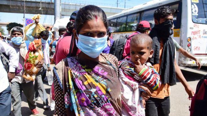 Una mujer migrante con un niño en sus brazos en la terminal de autobuses en Anand, India.