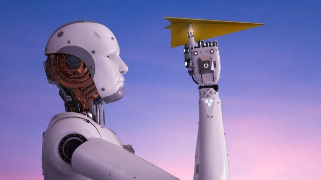 Un robot con un avión de papel doblado