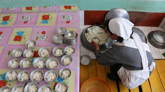 woman seen from above serving rice into small bowls