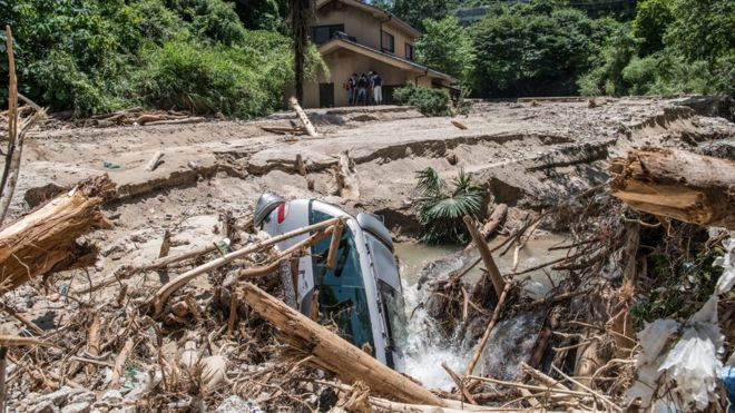 A car lies in mud as people rest in the shade of a house that is