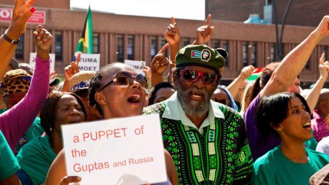 Протестующие держат в руках плакаты с критикой связей президента Зумы с семьей Гупта и с Россией в Порт-Элизабет, Южная Африка (04 апреля 2017 г.)