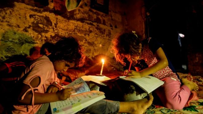 Palestinian children do homeowrk by candlelight September 2017