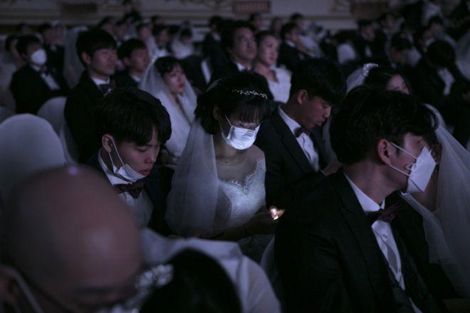 عروس ترتدي قناعاً واقياً، تعمل على هاتفها خلال حفل زفاف جماعي نظمته كنيسة التوحيد في غابيونغ