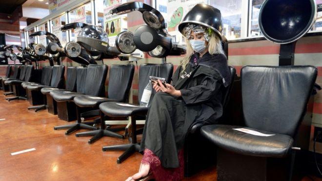 زبون يرتدي قناع وجه يجلس تحت مجفف في صالون فارغ في ماريتا ، جورجيا