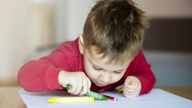 Young boy colouring in paper