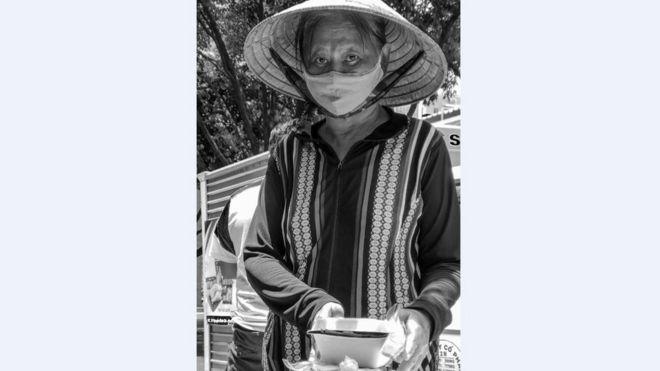 Bà cụ đội nón lá đi kiếm bữa trưa cho mình, lúc 11 giờ trên đường Nguyễn Văn Thủ, Q1