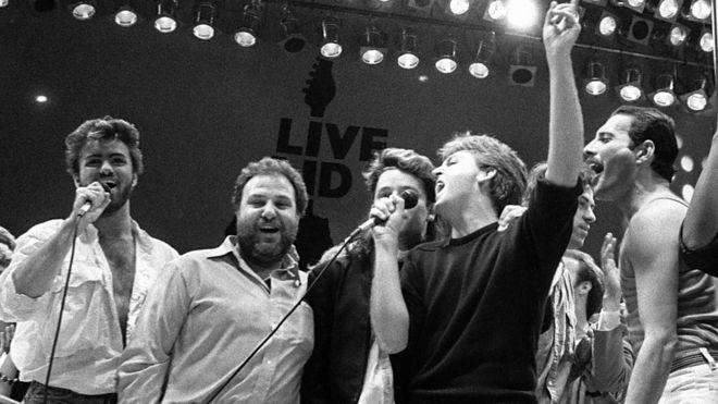 Michael (à esquerda) esteve no palco na despedida final do Live Aid, ao lado do promotor do evento Harvey Goldsmith e dos músicos Bono, Paul McCartney, Bob Geldof e Freddie Mercury.